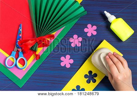 Making gift for Mother's Day by the child. Colorful bouquet of flowers out of paper. Children's art project. DIY concept. Step-by-step photo instruction. Step 4. Child cut flowers with special puncher