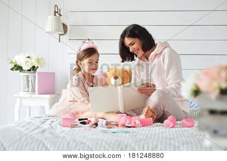 Mother and her daughter are interested by a book they are looking at. They are sitting on the bed among mess of girlish stuff