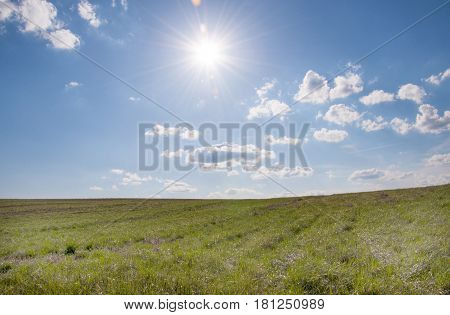 The sun shines over a grassy field and clouds int he sky.