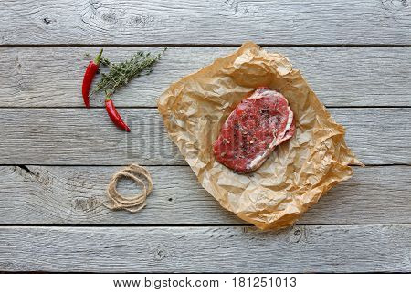 Raw beef steak in craft paper on dark wooden table background, top view. Fresh juicy meat, rosemary and chili peppers. Cooking ingredients, butcher's and grocery concept