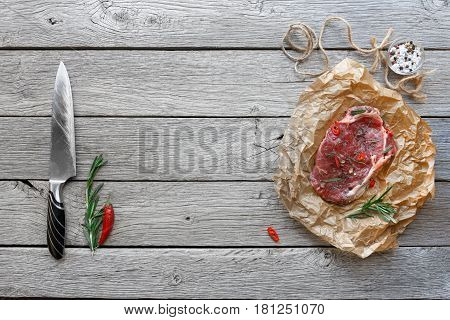 Raw beef steak in craft paper on dark wooden table background, top view with copy space. Fresh juicy meat, knife, rosemary and chili peppers. Cooking ingredients, butcher's and grocery concept