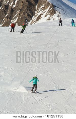 Women Snowboarder Snowboarding On Fresh White Snow With Ski Slope On Sunny Winter Day
