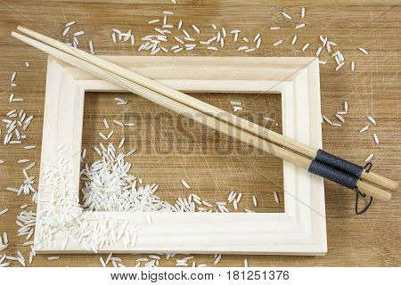 Chopsticks with rice and frame on the light wooden background