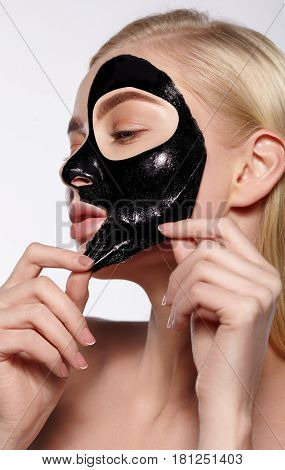 The girl takes off a black cosmetic mask from her face.