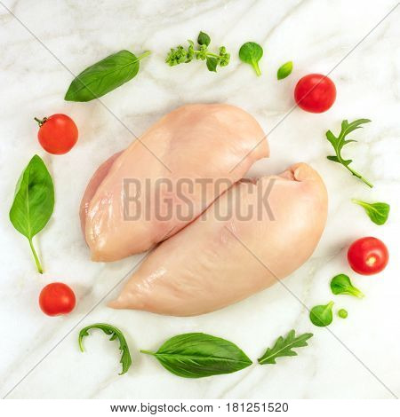 A square photo of chicken fillets with cherry tomatoes, fresh herbs including basil leaves, corn salad, and ruccola, shot from above on a while marble table with a place for text