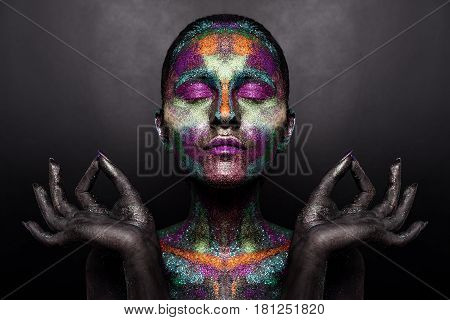 Young artistic woman in black paint and colourful powder. Glowing dark makeup. Creative body art on the theme of space and stars. Bodypainting project: art, beauty, fashion
