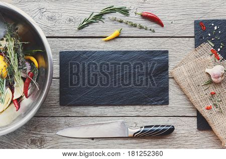 Cooking meat background. Knife, black stone cutting board, herbs, fresh vegetables, garlic and other seasoning frame on rustic wood, top view. Menu or recipe mockup