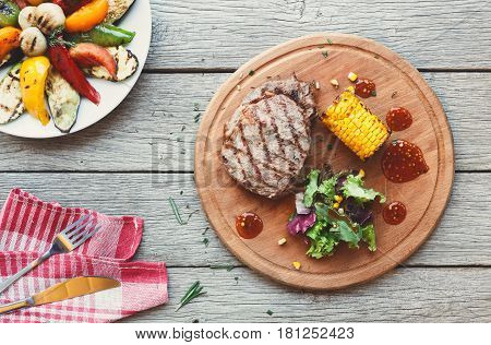 Grilled beef steak cooked on barbecue, top view on rustic wood background. Fresh juicy roasted red meat on round wooden board, with corn and vegetables. Restaurant food, delicious dish