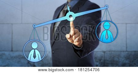 White collar employee icon is outweighing a blue collar worker symbol on a virtual pair of scales. Business concept for human resources management pay gap workplace discrimination and mediation.
