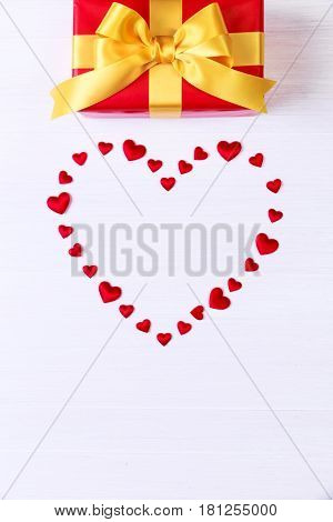 Gift box with red heart. Present wrapped with yellow ribbon. Christmas or birthday package. On white wooden table.