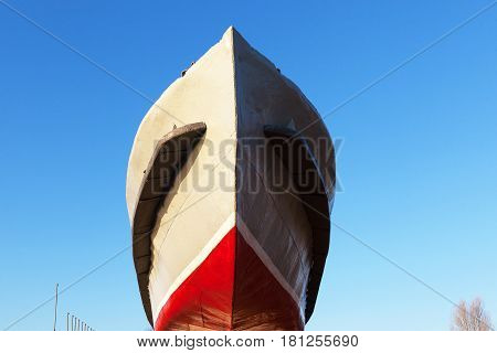 The ship stern painted red and gray color against the background of the blue sky