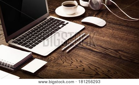 Modern devices, Mobile with black screen on laptop. Wooden desktop