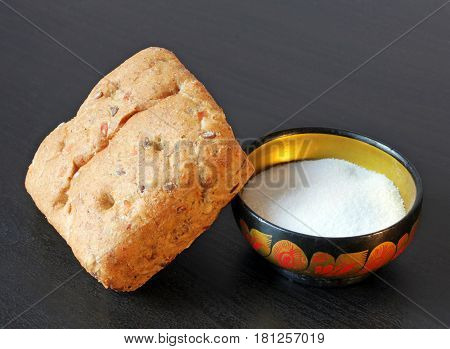 Closeup view of fresh bread bun and beautiful vintage saltcellar on black wooden table.