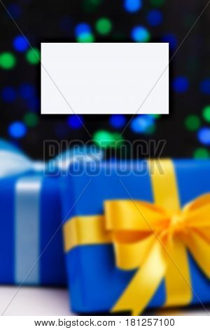 Business card mockup. Gift boxes on blurred background. Presents wrapped with paper, bow and ribbons. Christmas or birthday packages.