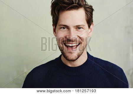 Happy stubble guy in blue portrait studio shot