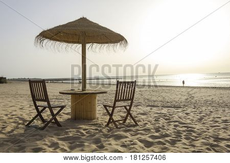 Wooden table and chairs with umbrella on the beach at sunset