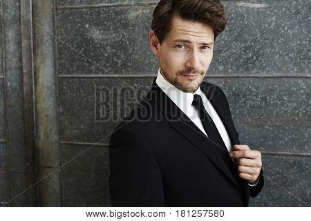 Suave businessman in black portrait studio shot