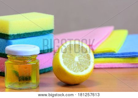 Cleaning sponge with scrub and rags set, olive oil, lemon on a wooden table. Eco house cleaning concept. Closeup