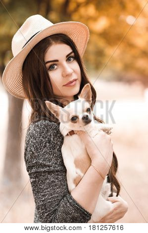 Smiling stylish girl 24-29 year old holding chihuahua puppy outdoors. Looking at camera. 20s.