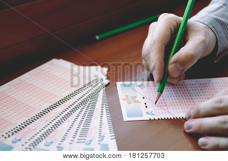 WROCLAW POLAND - MARCH 28th 2017: Man fill out a lotto lottery ticket. Lottery organized by Totalizator Sportowy. It has been in Poland since 1957.