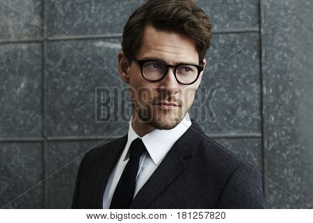 Suave man in spectacles and suit looking away