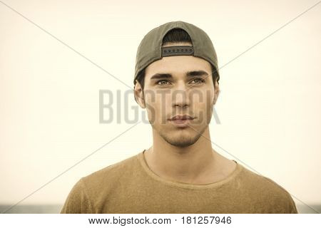 Portrait of handsome young man outside wearing baseball cap, looking at camera. Head and shoulders shot
