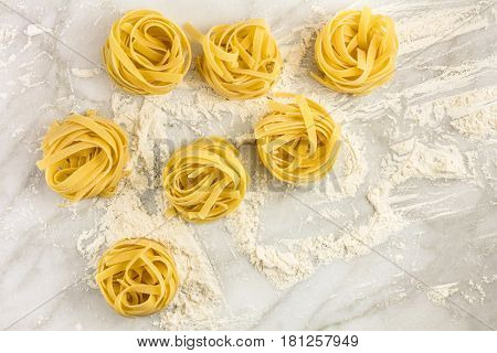 An overhead photo of pasta nests on a white marble table with flour and a place for text