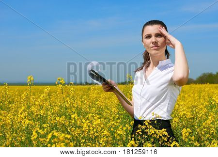 Business woman in flower field outdoor with clipboard look into the distance. Young girl in yellow rapeseed field. Beautiful spring landscape, bright sunny day