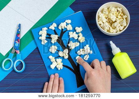 Making card by a child on spring theme. Blossoming tree on a blue background. Original children's art project. DIY concept. Step-by-step photo instruction. Step 5. Child glues flowers from popcorn