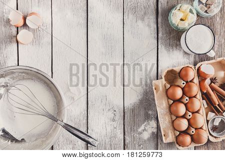 Baking background. Cooking ingredients and utencils for dough and pastry on sprinkled with flour rustic wood. Top view with copy space, mockup for menu, recipe or culinary classes.