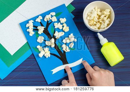 Making card by a child on spring theme. Blossoming tree on a blue background. Original children's art project. DIY concept. Step-by-step photo instruction. Step 6. Child glues tape for inscription