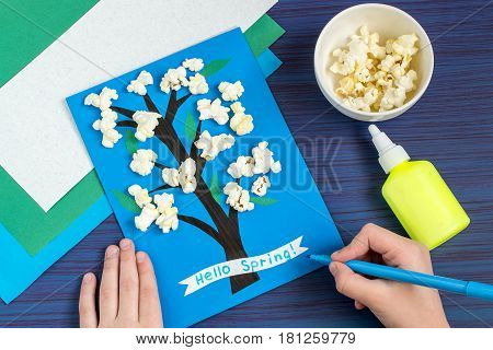 Making card by a child on spring theme. Blossoming tree on a blue background. Original children's art project. DIY concept. Step-by-step photo instruction. Step 7. Child writes: Hello spring