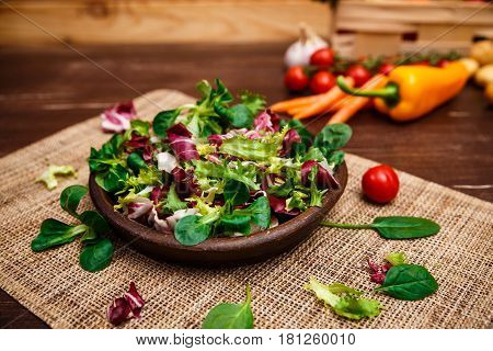 Provence salad. Leaves of endive or chicory, lamb and rose salad. Cherry tomato, pepper and carrot. Raw vegetables. On wooden table.
