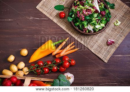 Provence salad. Leaves of endive or chicory, lamb and rose salad. Cherry tomatoes and carrot. Raw vegetables. On wooden table.