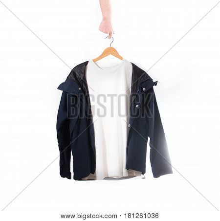 Hand Holds A White T-shirt And Black Jacket  On A Hanger On A White Background