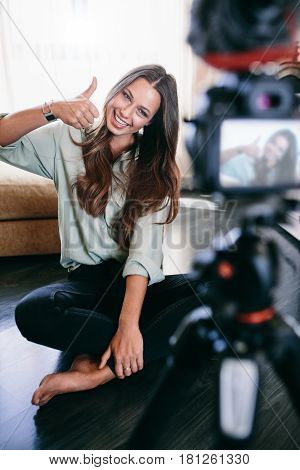 Beautiful Girl Recording Video On Tripod Camera In Her Living Ro