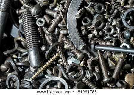 A large number of metal parts, removed macro bolts, nuts, springs, self-tapping screws