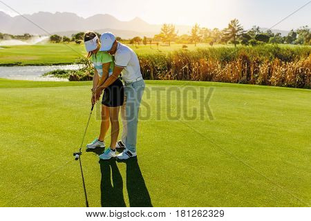 Male Instructor Showing Woman To Play Golf