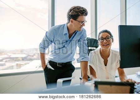 Happy business colleagues working together at their desk. Asian woman with male colleague in modern office.