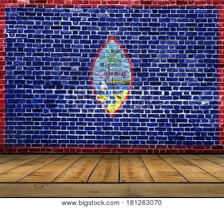 Guam flag painted on brick wall with wooden floor