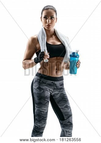 Beautiful athletic woman with towel on shoulders holding protein cocktail in shaker. Health concept.