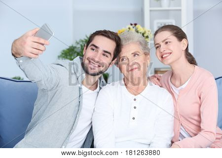 Grandmother and grandchildren taking selfie on sofa at home