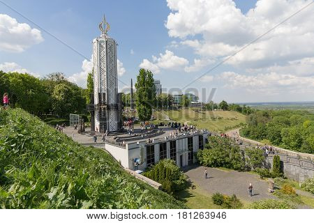 Kiev Ukraine - May o9 2016: Monument to victims of Holodomor and Domes of Kiev-Pechersk Lavra in Kiev on green hills of Pechersk