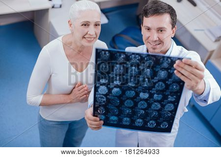 Such a relief. Cheerful nice elderly woman looking at the X ray photo and being relieved while having no physical deviations