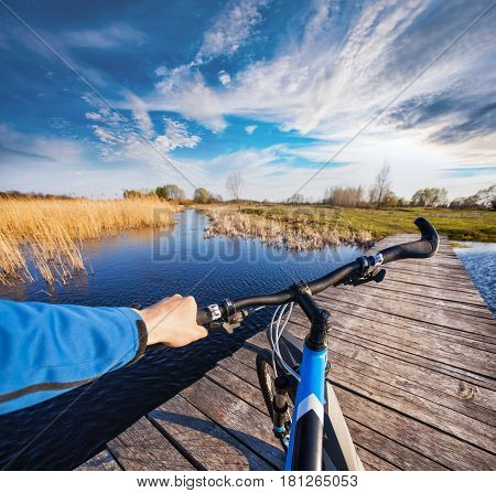 Man riding on a bicycle across the wooden bridge on the lake