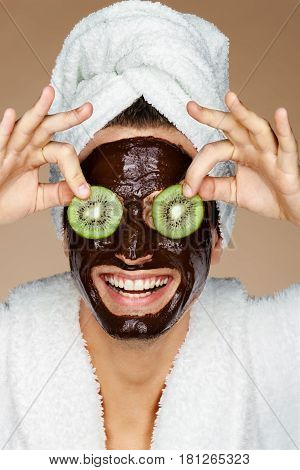 Laughing man receiving spa treatments. Photo of young man with pieces of kiwi in his eyes and chocolate face mask. Beauty & Skin care concept