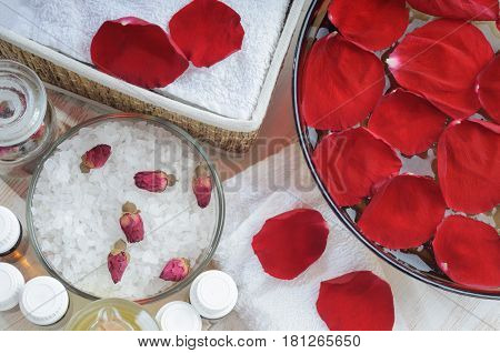 Accessories for manicure: hand bath with rose petals, essentials oils, bath salt, towels. Overhead view. Beauty and spa concept
