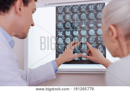 The problem is here. Nice aged grey haired woman looking at the brain X ray image and pointing at it while standing with her doctor