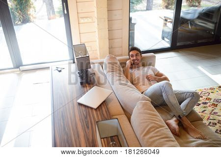 Cheerful young man looking away while lying on couch and talking on phone