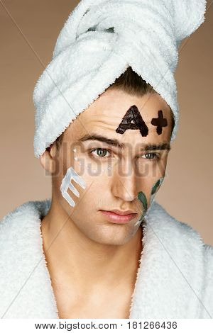 Vitamin E Vitamin A written on man's face. Photo of Well groomed man receiving spa treatments. Beauty & Skin care concept